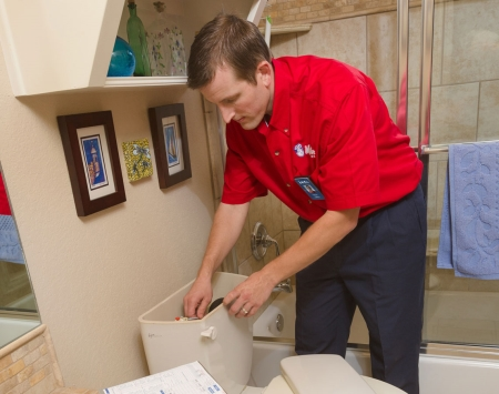Mr. Rooter technician fixing a toilet
